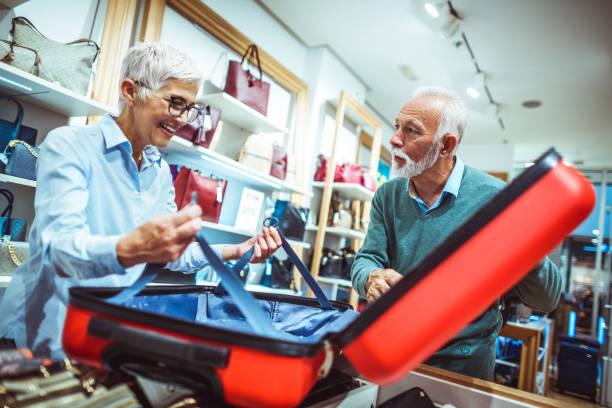 ältere frau, die dehnbare sicherheit riemen in einem roten koffer im ladengeschäft taschen und geldbörsen mit ihrem partner ausprobieren - trolley kaufen stock-fotos und bilder