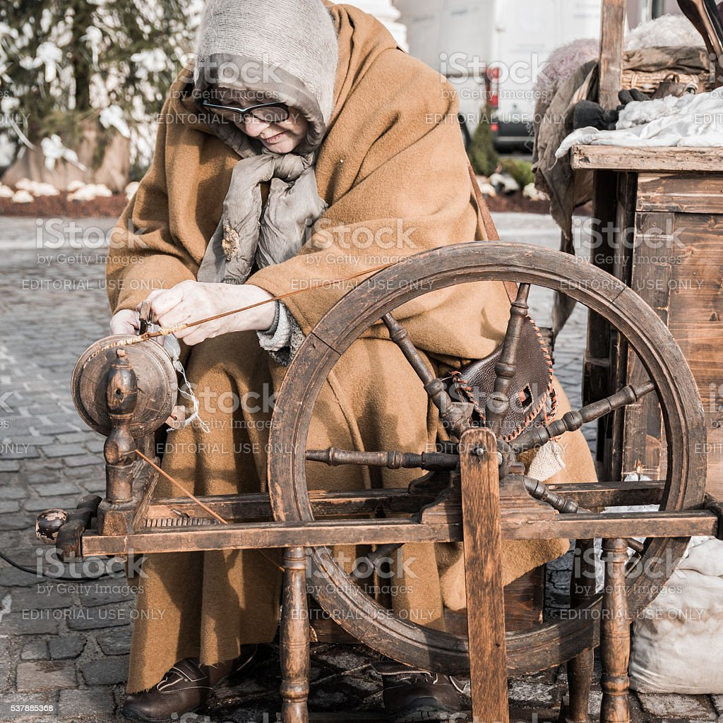 Elderly woman uses the cocoons of silkworms to spin. stock photo