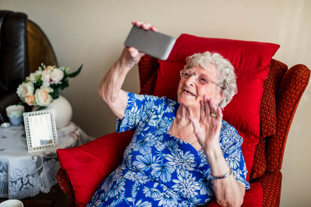 Elderly Woman Using A Mobile Telephone An elderly woman is using a smartphone. She is in a nursing home in Newcastle upon Tyne, North East England. northeastern england stock pictures, royalty-free photos & images