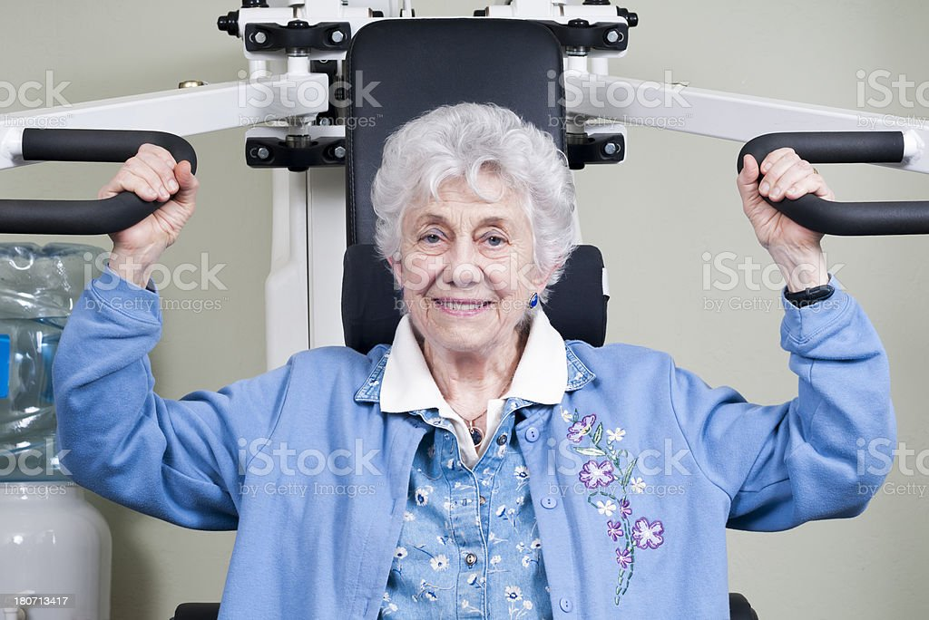Elderly Woman Using Arm Weight Machine royalty-free stock photo