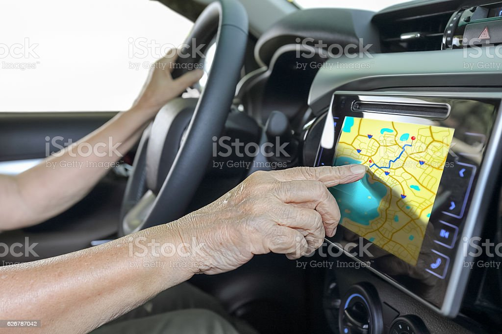 Elderly woman using GPS navigation system in car stock photo