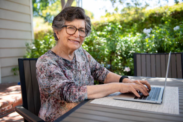 Elderly Woman Using Her Laptop Computer and Smart Technology A senior citizen types on her laptop at her patio table in the backyard. She is wearing a smart watch. armenian ethnicity stock pictures, royalty-free photos & images
