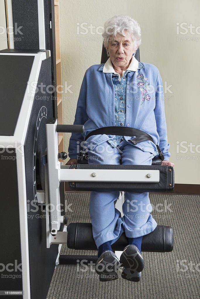 Elderly Woman Using Leg Curl Weight Machine royalty-free stock photo