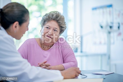 An elderly woman sits at a desk across from her female doctor.  The woman is wearing a pink shirt and the doctor is dressed in a white lab coat.  The doctor has her back to the camera and they are discussing the patients chart