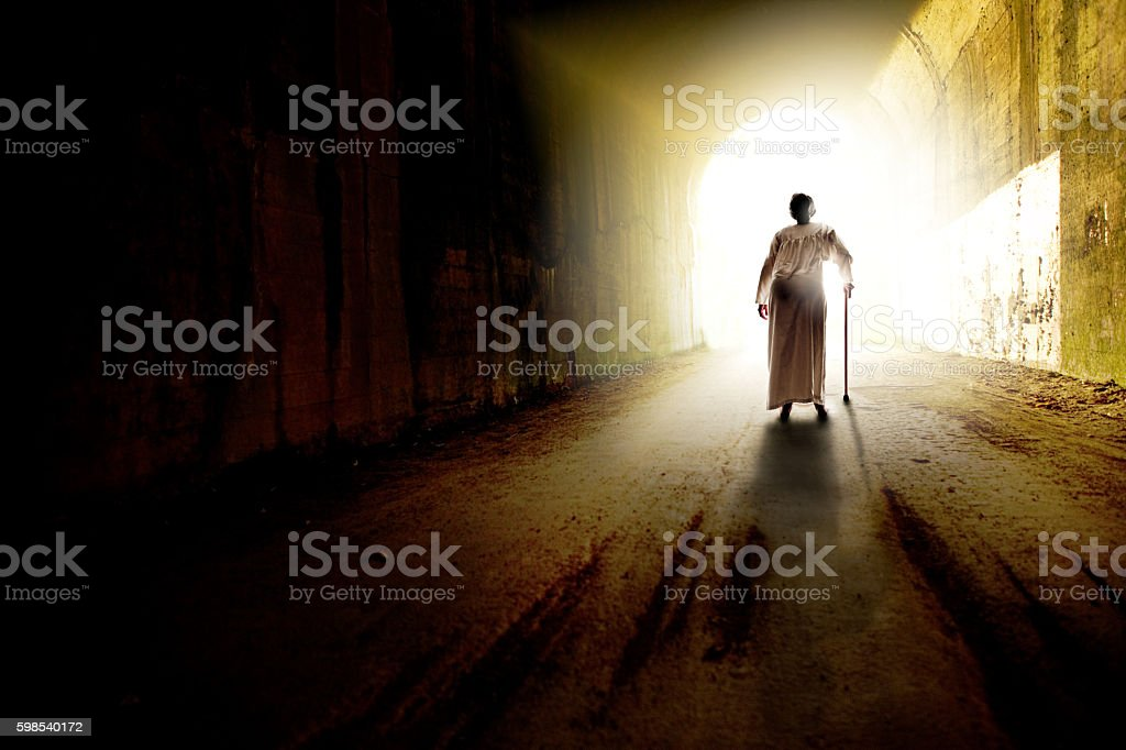 Elderly Woman Walking Towards Light The figure of an elderly woman walking toward the light a the end of a tunnel. Achievement Stock Photo