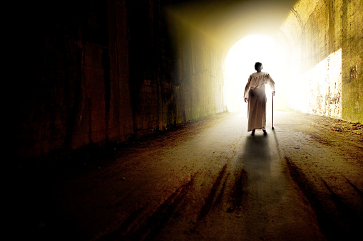Elderly Woman Walking Towards Light Stock Photo - Download Image Now