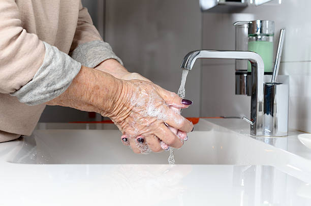 Elderly woman washing hands under tap bildbanksfoto