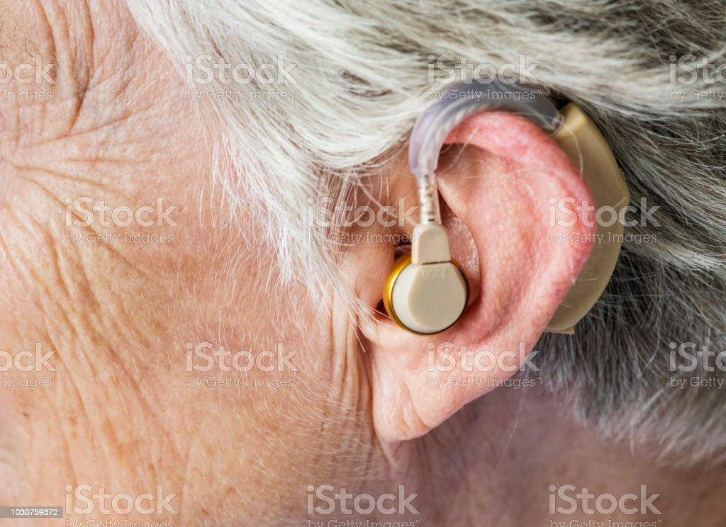 Elderly woman wearing a hearing aid stock photo