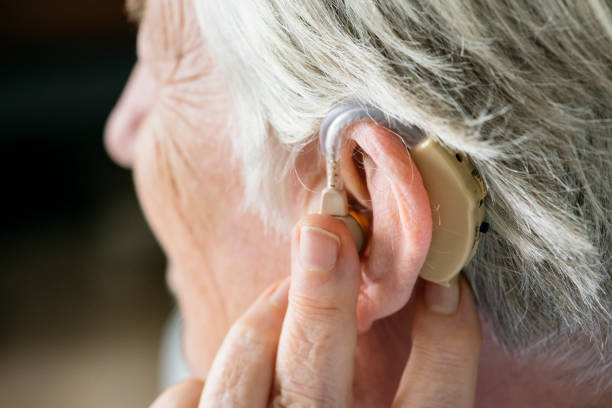 elderly woman wearing a hearing aid - sordità foto e immagini stock