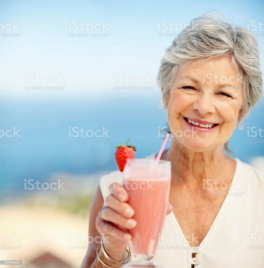 Elderly woman with a glass of strawberry milkshake royalty-free stock photo