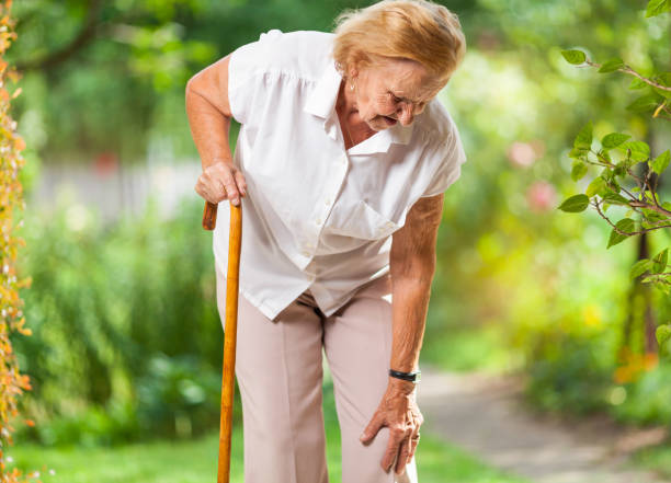 Elderly woman with a walking stick stock photo