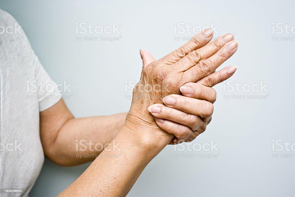 Mujer de edad avanzada con artritis en sus manos - foto de stock