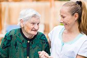 istock Elderly woman with caregiver 671767154