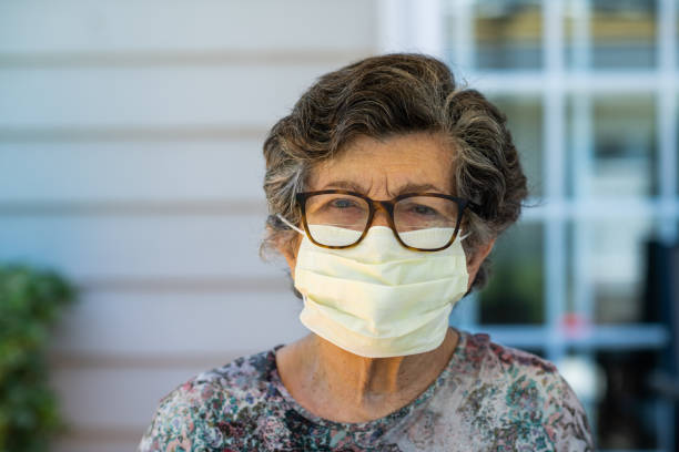 Elderly Woman with Facemask Portrait A senior citizen with face-mask and glasses looking into camera with a serious face armenian ethnicity stock pictures, royalty-free photos & images