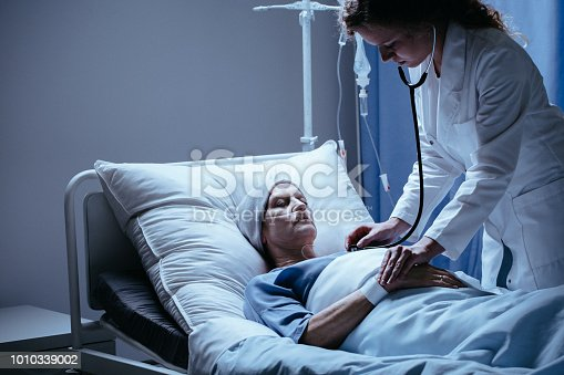 928968772 istock photo Elderly woman with headscarf in hospital bed while doctor checking life functions 1010339002