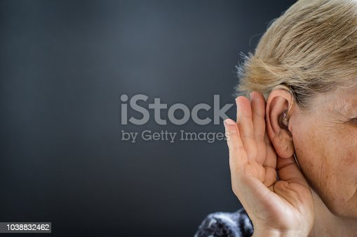 istock Elderly woman with hearing aid on black, grey background. Deafness concept. 1038832462