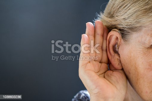 istock Elderly woman with hearing loss on grey background. Age related health problem. 1038833236