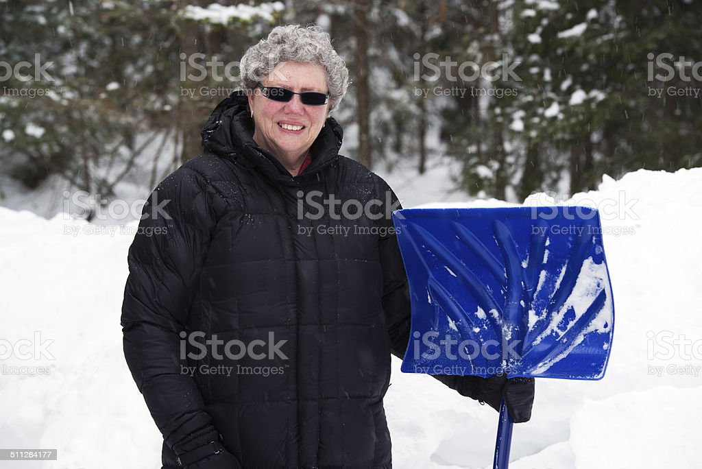 Elderly Woman with Snow Shovel stock photo