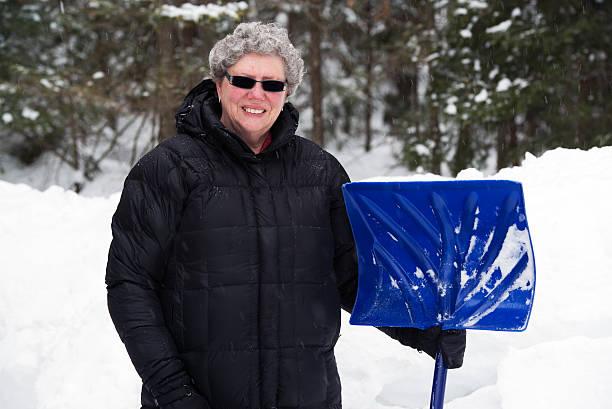Elderly Woman with Snow Shovel stock photo