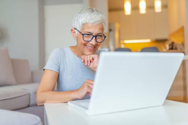 Elderly woman working on laptop computer, smiling. Close-up portrait of casual woman using her laptop while sitting on couch and working. An attractive middle aged businesswoman sitting in front of laptop and managing her small business from home. electronic banking stock pictures, royalty-free photos & images