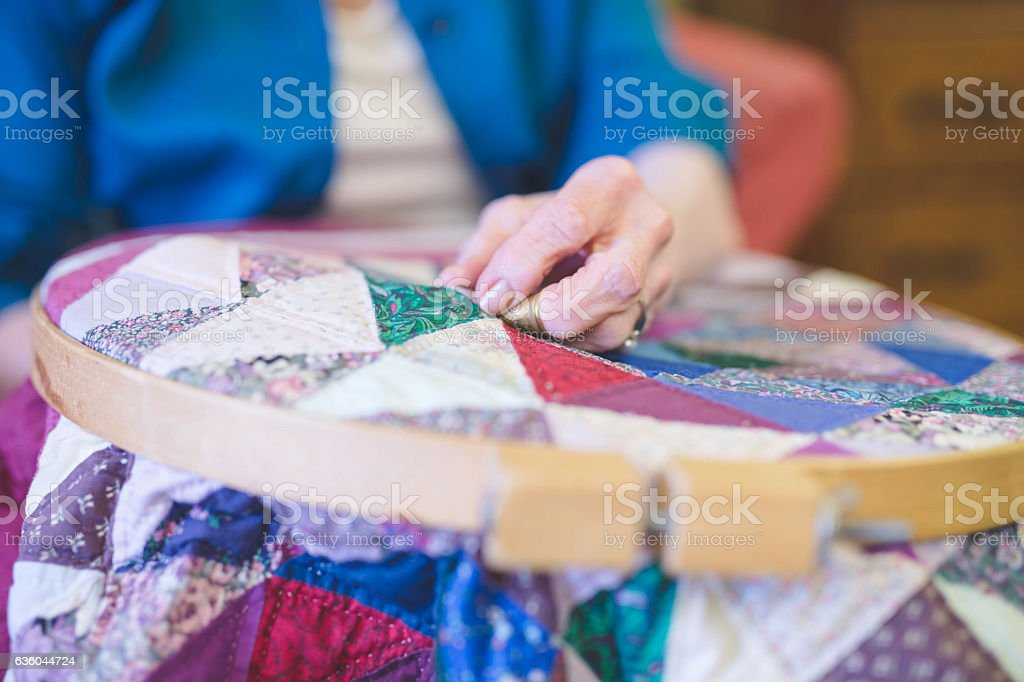 Elderly womans hand crocheting a quilt stock photo