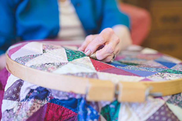 elderly womans hand crocheting a quilt - quilt stock photos and pictures