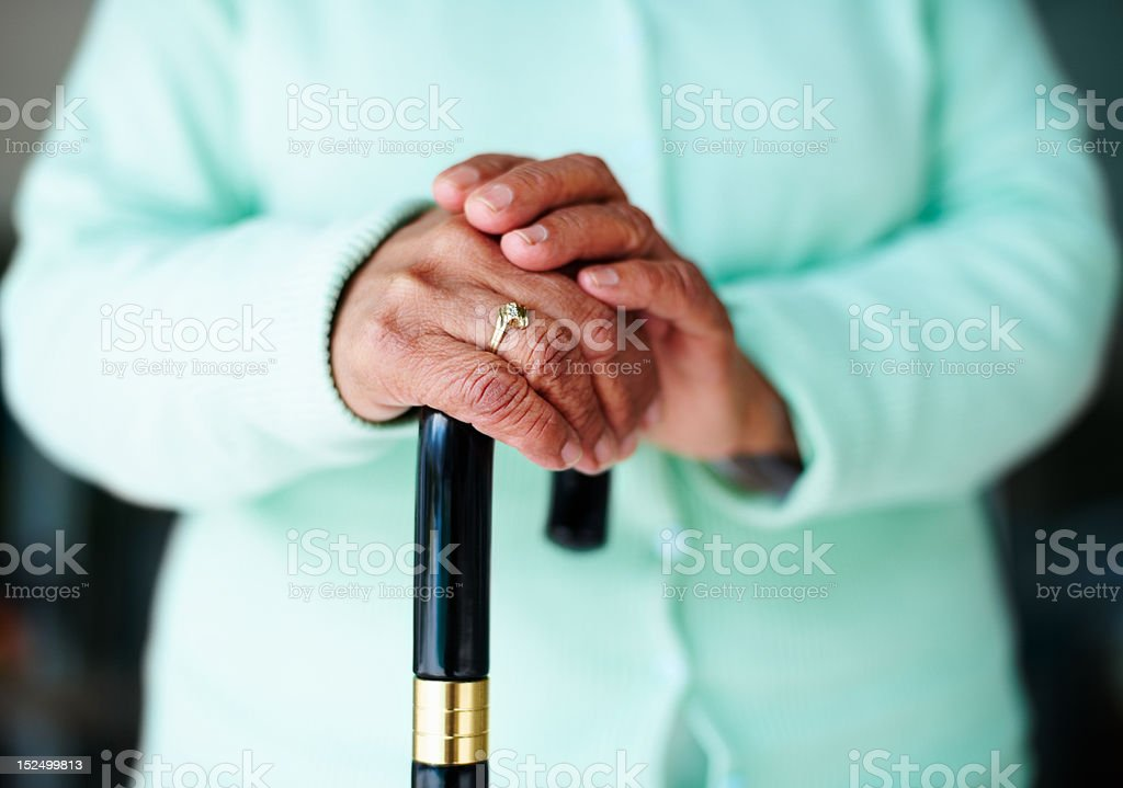 Elderly woman's hand on a walking stick royalty-free stock photo