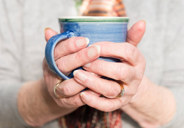 Elderly woman's hands holding a hot drink stock photo
