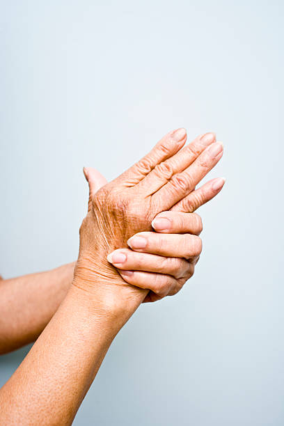 Elderly woman's with arthritis in her hands stock photo