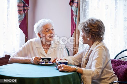 Elderly women (80s) drinking tea or coffee together at table, having conversation.  Focus on woman on left.
