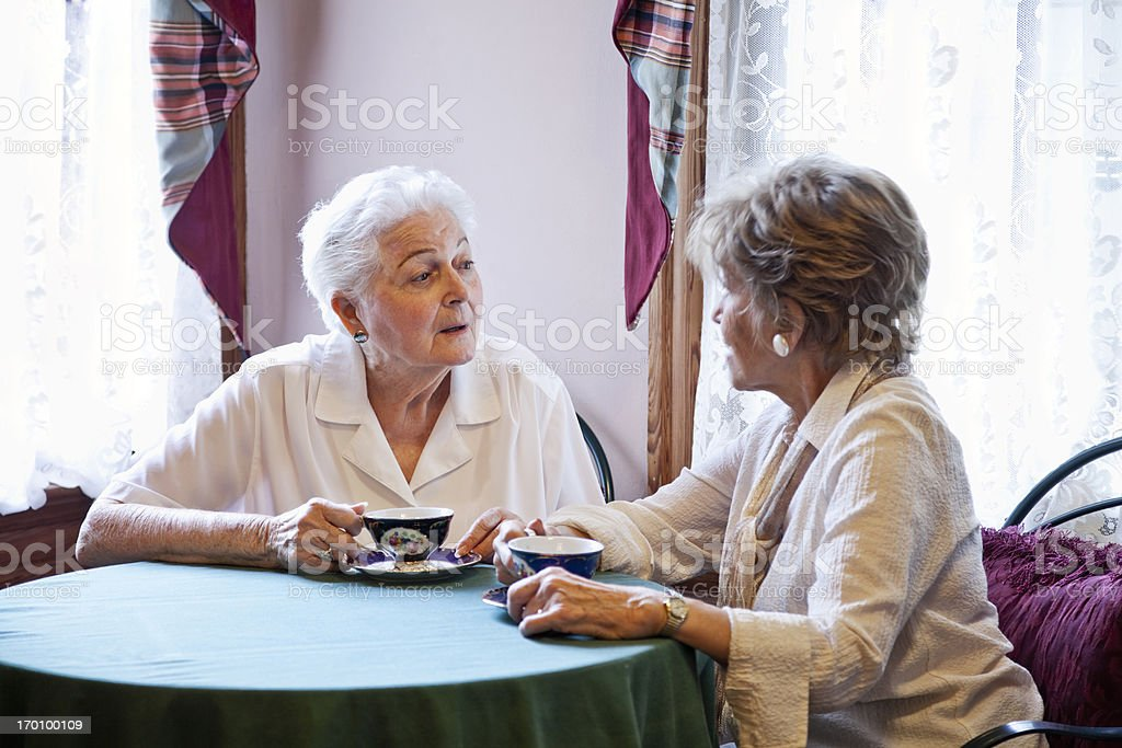 Elderly women drinking tea and talking stock photo