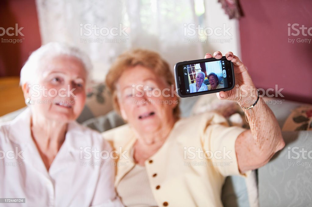 Elderly women photographing themselves stock photo