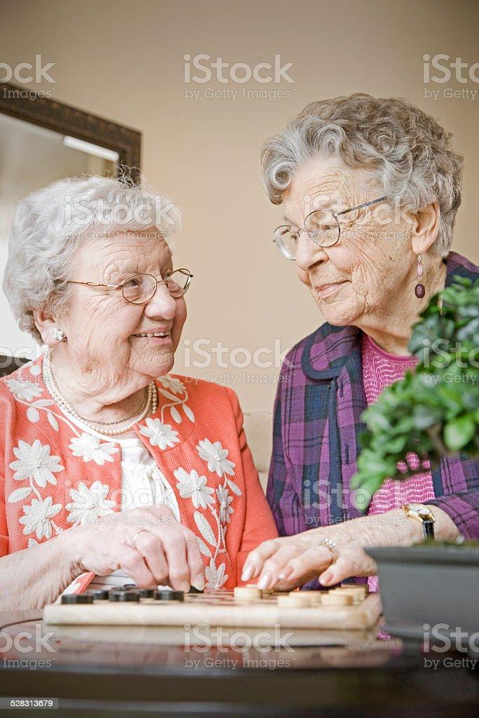 Elderly Women Playing Checkers in Nursing Home stock photo
