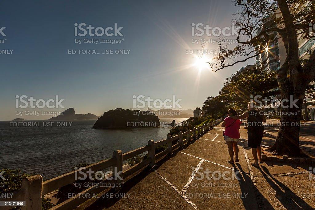 Eldery Couple Walking by Coastline at Sunset stock photo