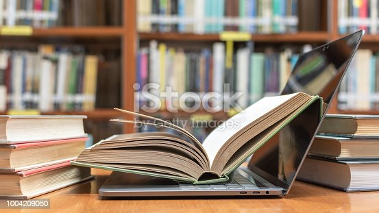 istock E-learning class and e-book digital technology in education concept with pc computer notebook open in blur school library or classroom background among old stacks of book, textbook archive collection 1004209050