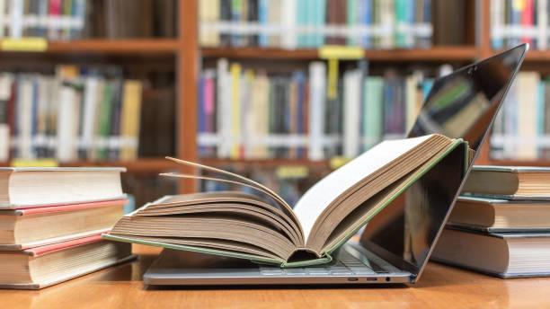 tecnología digital e-learning clase y e-book en el concepto de educación con pc ordenador portátil abierto en desenfoque de fondo biblioteca o aula de la escuela entre viejo pilas de libros, colección de libros de texto de archivo - biblioteca fotografías e imágenes de stock