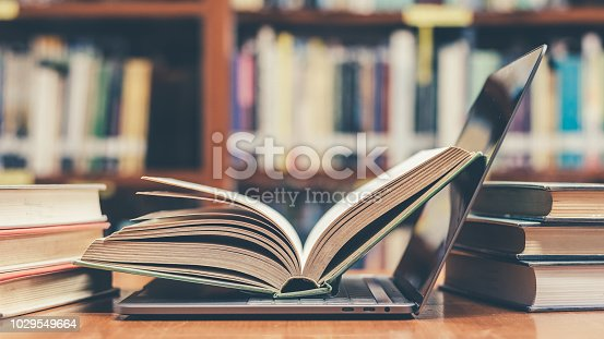 istock E-learning class and e-book digital technology in education concept with pc computer notebook open in blur school library or classroom background among old stacks of book, textbook archive collection 1029549664