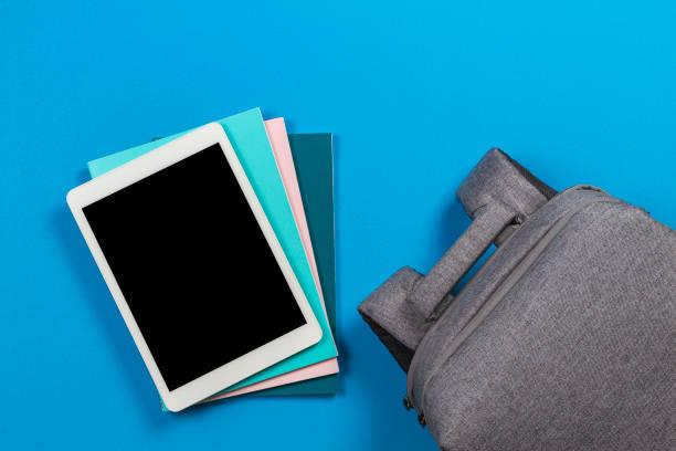 E-Learning-Konzept - leere Tablet-Computer auf Stapel von bunten Büchern und Notebooks und Rucksack auf blauem Hintergrund – Foto