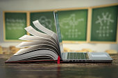 istock E-learning online education or internet  encyclopedia concept. Open laptop and book compilation in a classroom. 1263424631