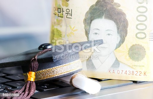 959387240 istock photo E-learning online graduate education concept : Graduation cap, certificate degree on laptop computer blur foreign money KRW bill money background. Elearning can learn distant by internet enhance study 946455950