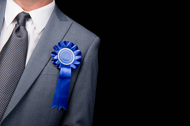 Election Candidate - Blue Rosette Grey suited man wearing a blue rosette, against a black background. civil servant stock pictures, royalty-free photos & images