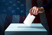 Election in America Concept. Hand Dropping a Ballot Card into the Vote Box, Flag of United States as background