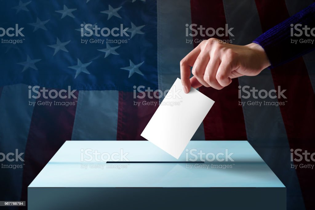 Election in America Concept. Hand Dropping a Ballot Card into the Vote Box, Flag of United States as background stock photo