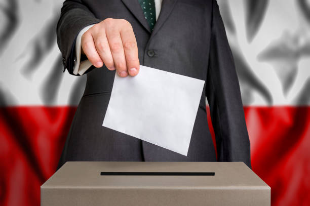 Election in Poland - voting at the ballot box Election in Poland - voting at the ballot box. The hand of man putting his vote in the ballot box. Flag of Poland on background. polish culture stock pictures, royalty-free photos & images