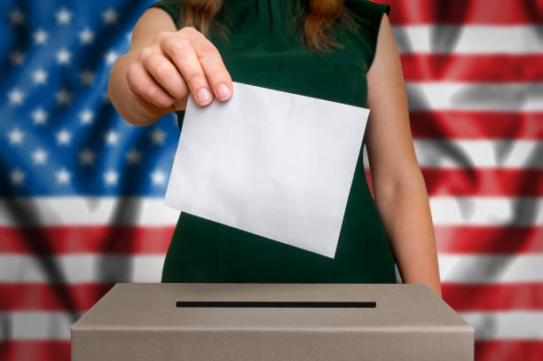 Election in USA - voting at the ballot box Election in United States of America - voting at the ballot box. The hand of woman putting her vote in the ballot box. Flag of USA on background. citizenship stock pictures, royalty-free photos & images