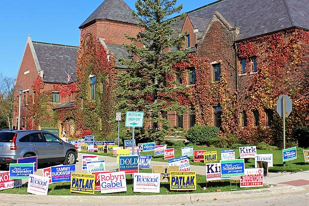 election political lawn signs outside polling place at village hall - vote sign stock photos and pictures