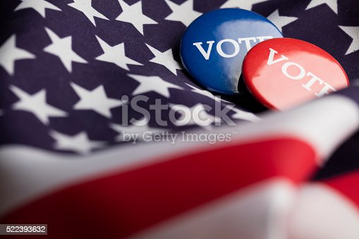 Red and blue election badges with the word vote written in white. The badges are on an american stars and stripes flag