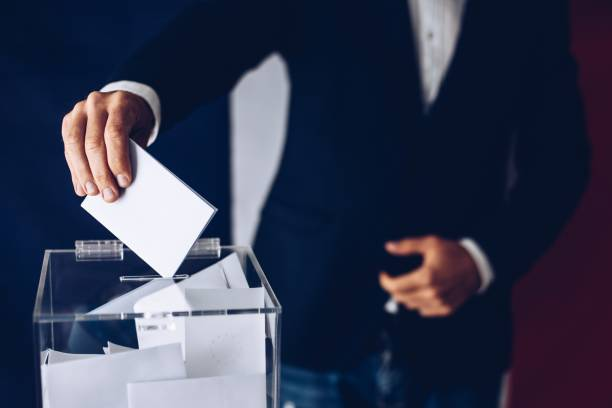 Elections in France. Man throwing his vote into the ballot box. stock photo