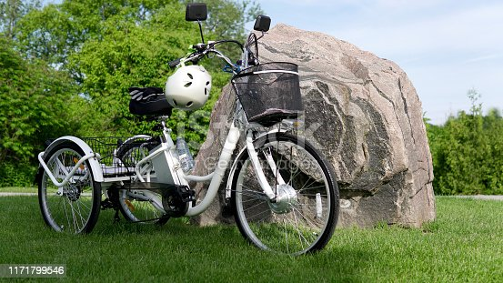 Electric bicycle on the green grass with stone background on sunny summer day. Shot from the side. A lot of natural lighting. The view of the e motor, power battery gear, hamlet and gloves.