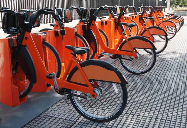 elektrofahrräder an einer fahrrad-sharing-station geparkt - elektrorad stock-fotos und bilder
